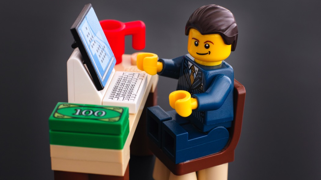 Tambov, Russian Federation - March 24, 2015: Lego businessman sits at his working table with computer, money and cup on black background. Studio shot.